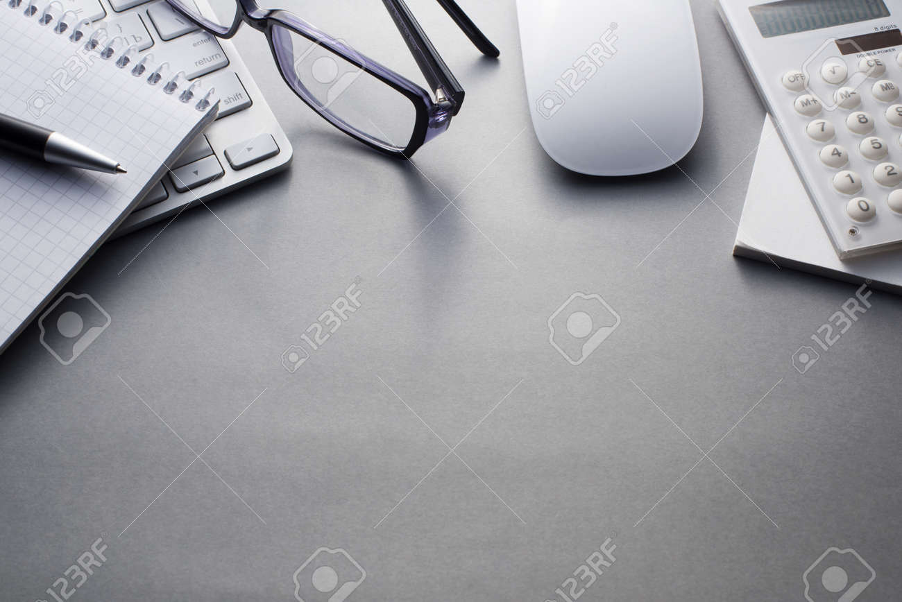 Angled View of Mac Computer Keyboard and Mouse with Various Office Supplies on Grey Desk with Ample Copy Space - 40628492