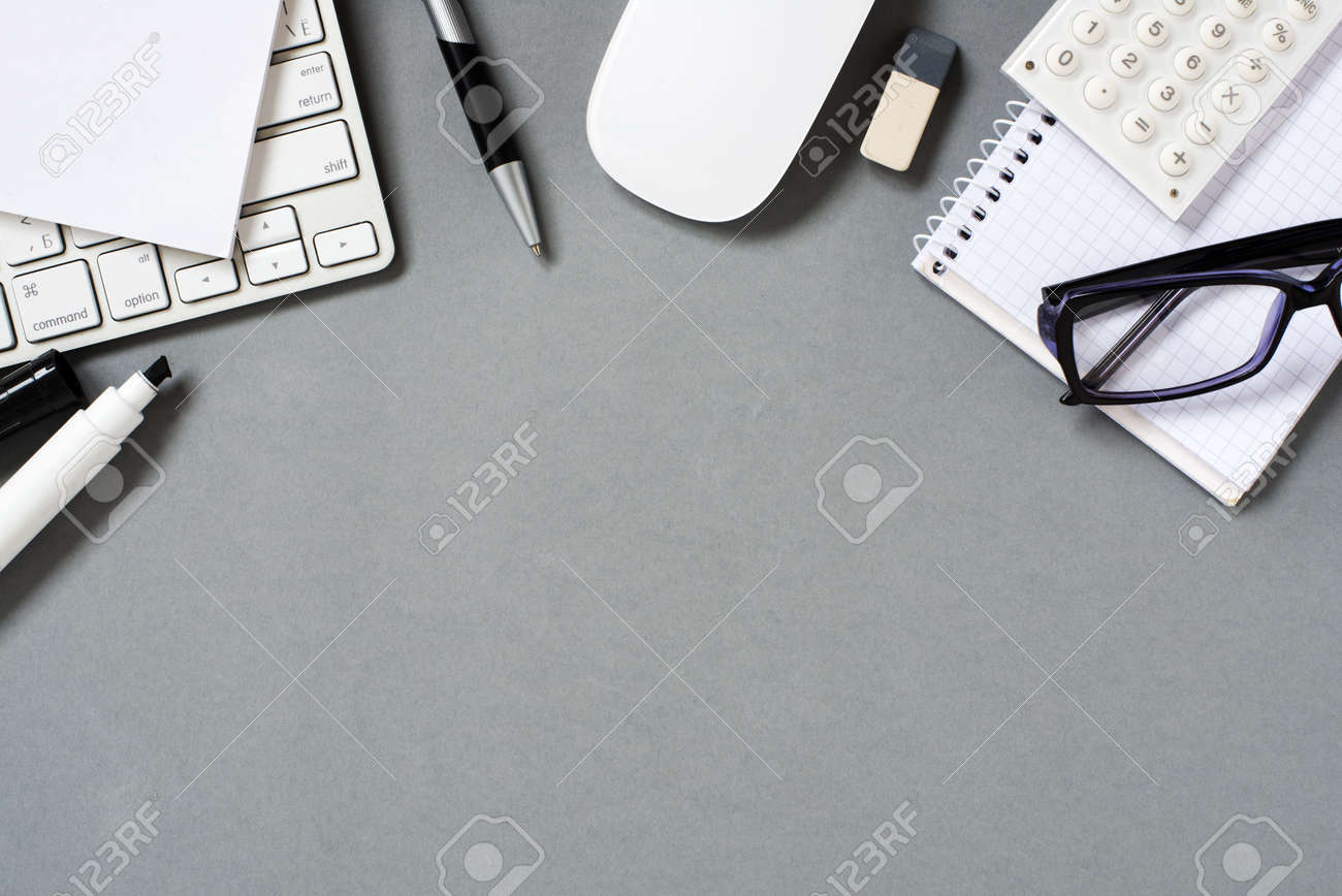 High Angle View of Mac Computer Keyboard and Mouse with Various Office Supplies and Eyeglasses Scattered on Grey Desk with Ample Copy Space - 40628496