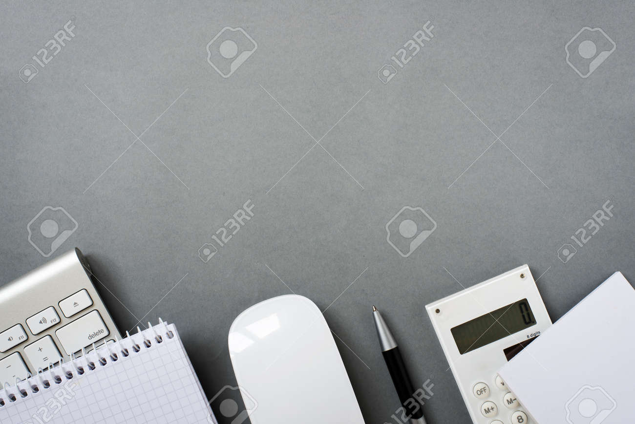 High Angle View of Mac Computer Keyboard and Mouse with Note Pads, Calculator and Pen on Grey Desk with Ample Copy Space - 40628500