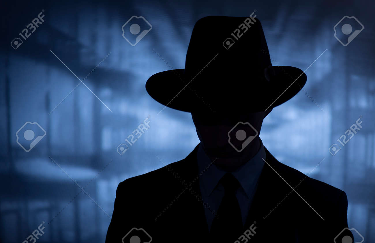 Silhouette of a mysterious man in a vintage style wide brimmed hat in a close up head and shoulders portrait - 67400551