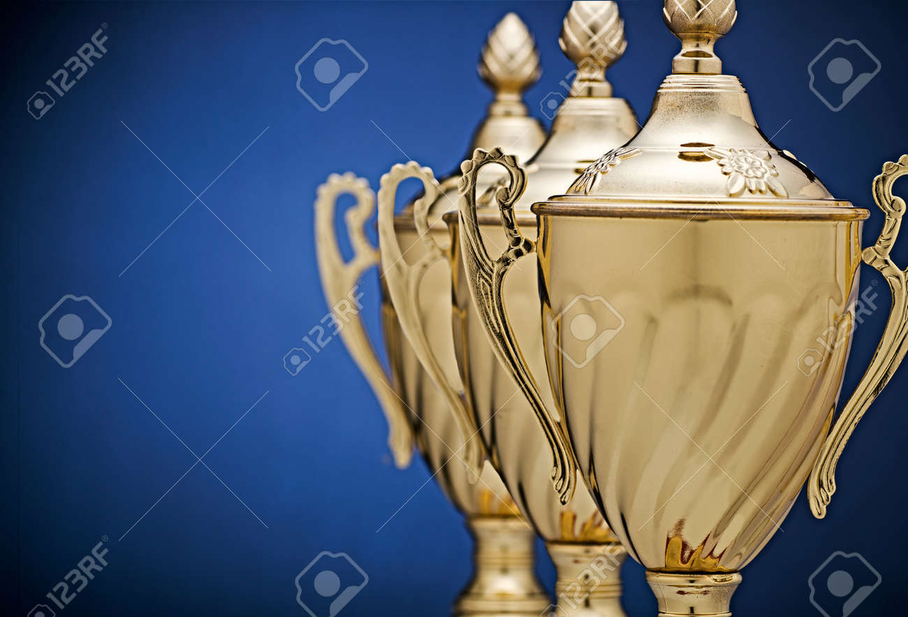 Receding staggered row of three gold trophy cups on a blue background with vignette and copy space conceptual of success, winning, challenge and competition - 71129196