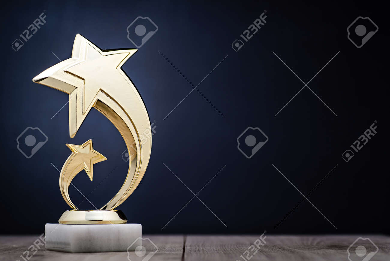 Elegant gold winners trophy with shooting stars to be awarded for the first place in a competition or championship over a dark blue background with copy space - 70947373