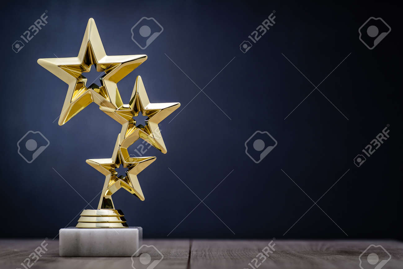 Gold winners award with three stars to be awarded to the first place in a competition or championship standing on a pedestal against a blue background with copy space - 70947374