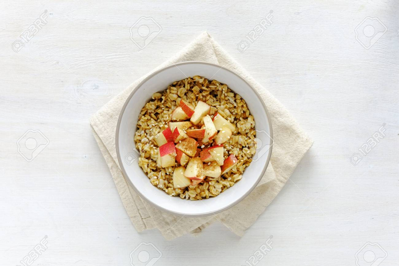Flat lay view of oatmeal with apple in bowl against white table - 114192418