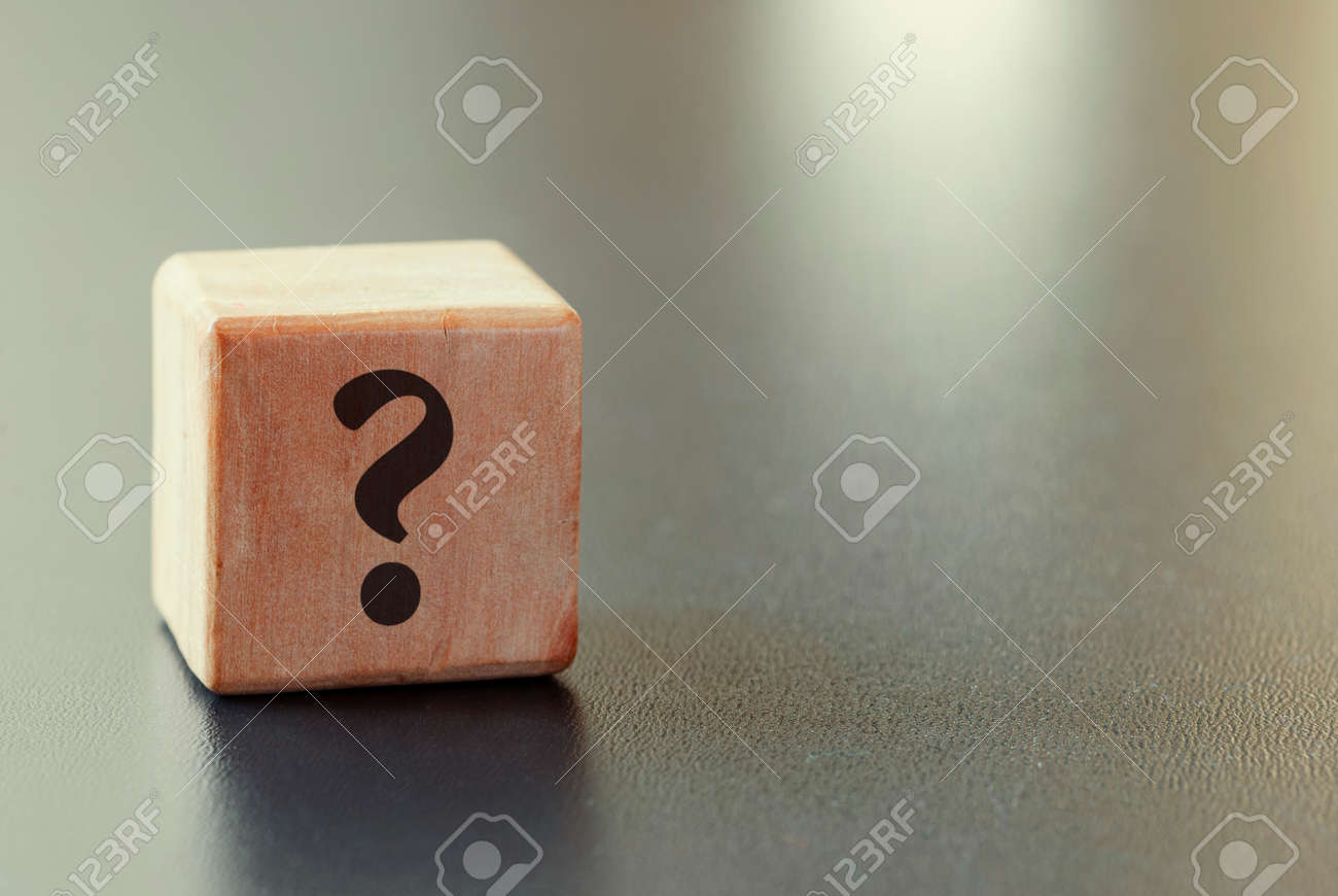 Small wooden toy block with question mark over a grey background with highlight and copy space in a conceptual image - 132223119