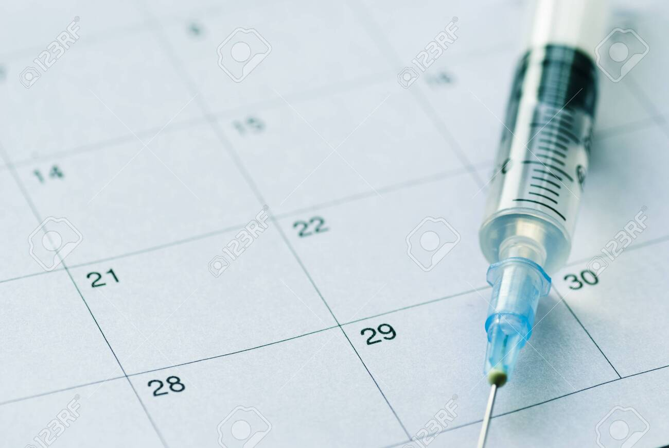 Medical syringe with transparent vaccine on white calendar background. Vaccination schedule concept with copy space - 131503204