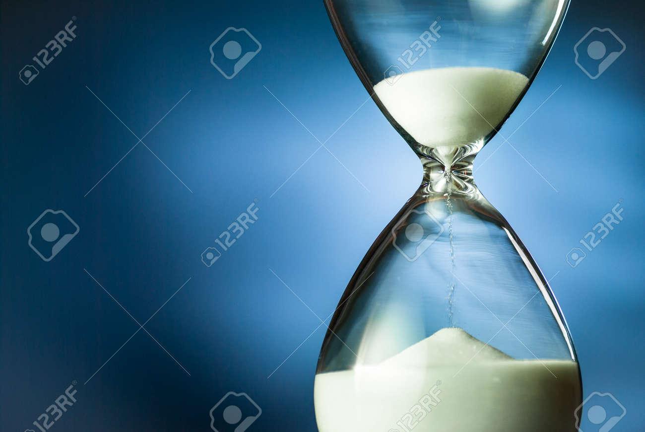 Sand running through an hourglass or egg timer - 135536964