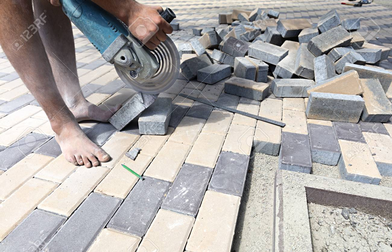 Stock Photo   The Worker Cuts A Bar Of Paving Slabs For The Final Laying On  The Terrace