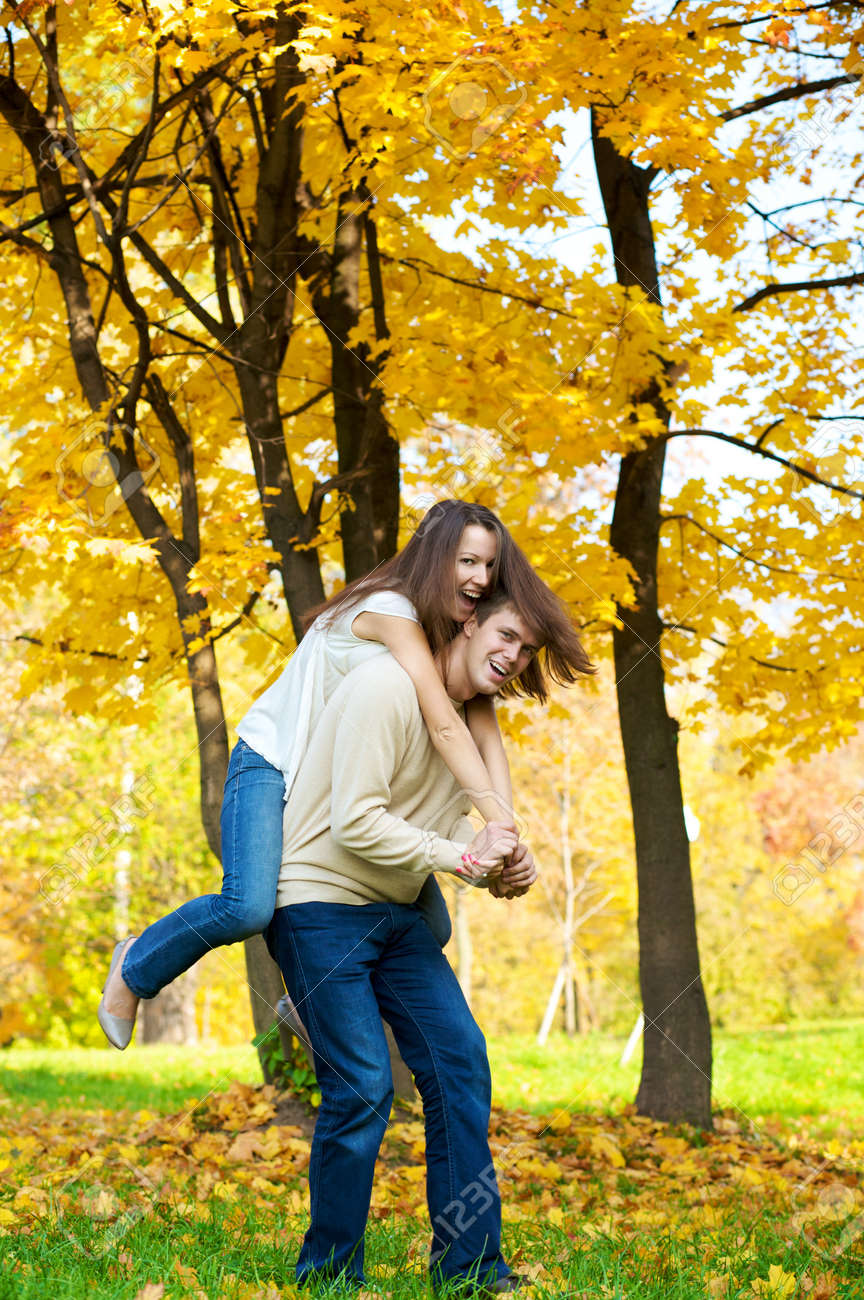 Happy young couple play piggyback in the autumn park Stock Photo - 4157567