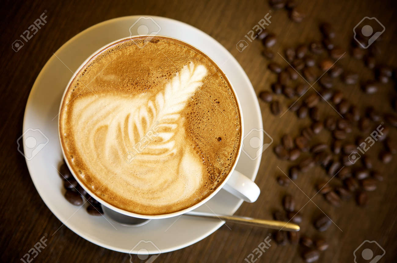 Latte art on a cappucinno and coffee-beans (selective DOF) Stock Photo - 6937293