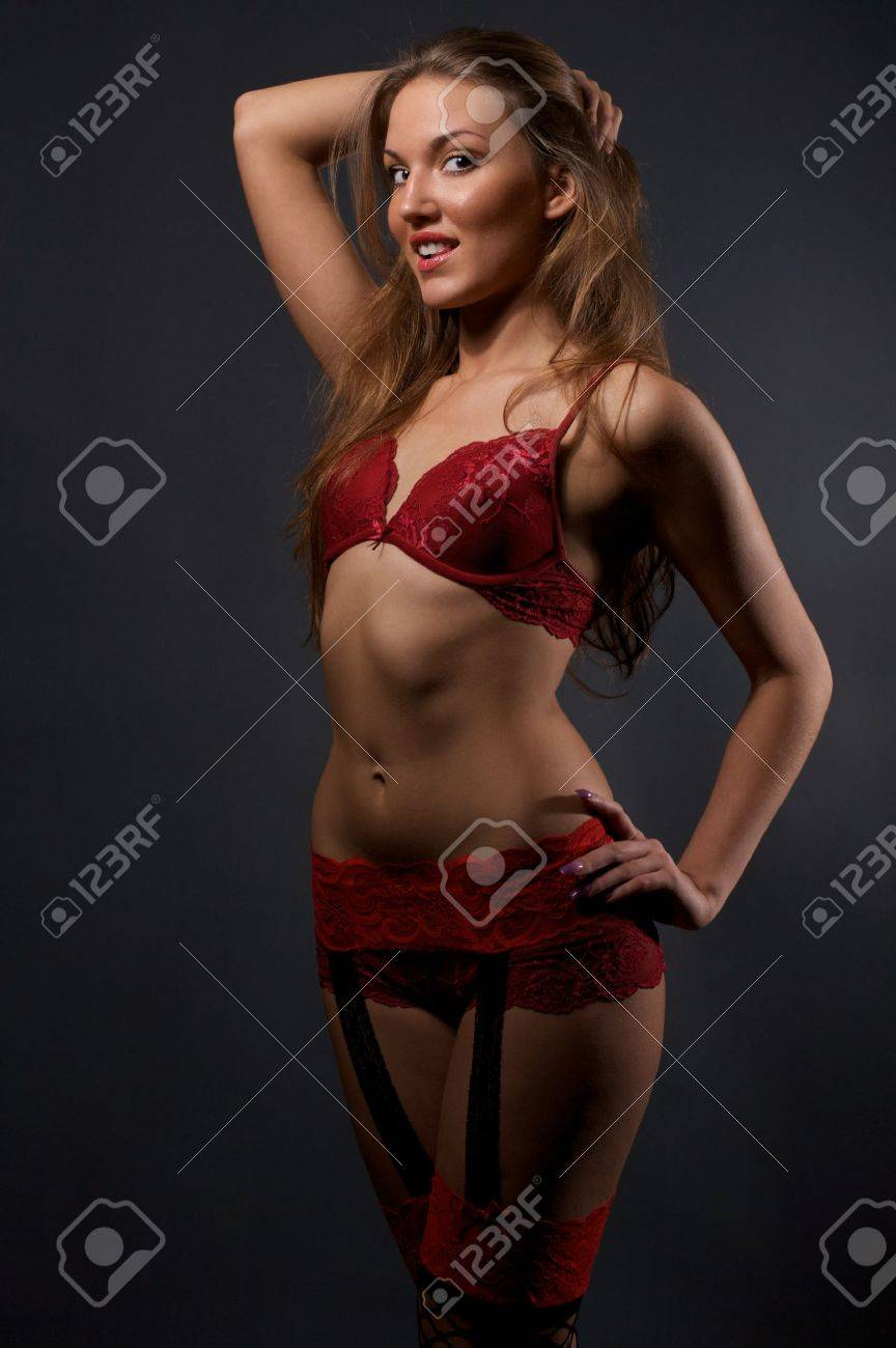 252cf2cdb Pretty young woman in red lingerie and stockings standing in the studio  Stock Photo - 6942332