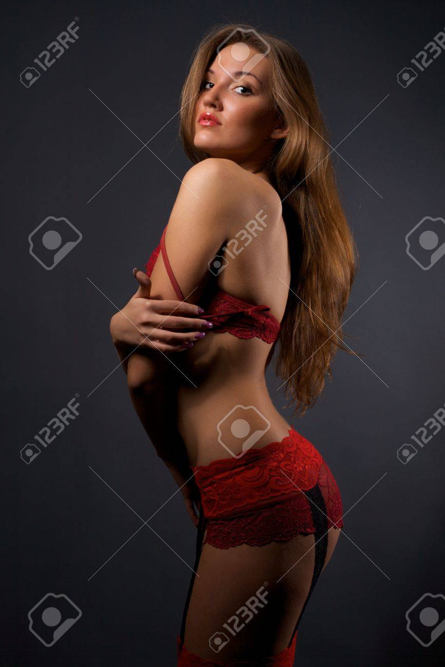 171d58fb5 Pretty young woman in red lingerie and stockings standing in the studio  Stock Photo - 6942302