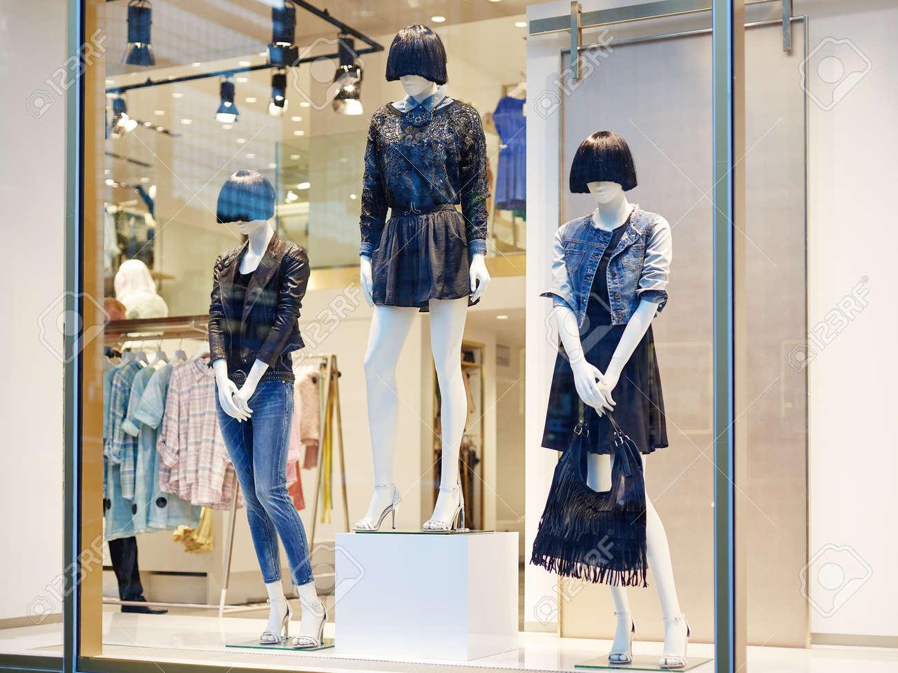 Mannequins standing in store window display of women s casual..