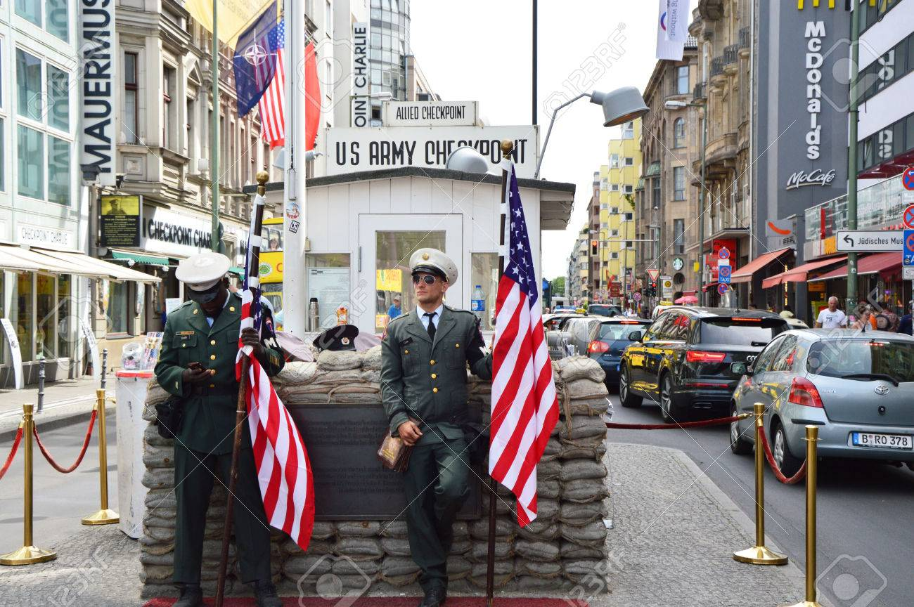 Checkpoint Charlie, famous passage between the West and East Berlin during the Cold War. American soldier standing guard holding the flag. - 81984235