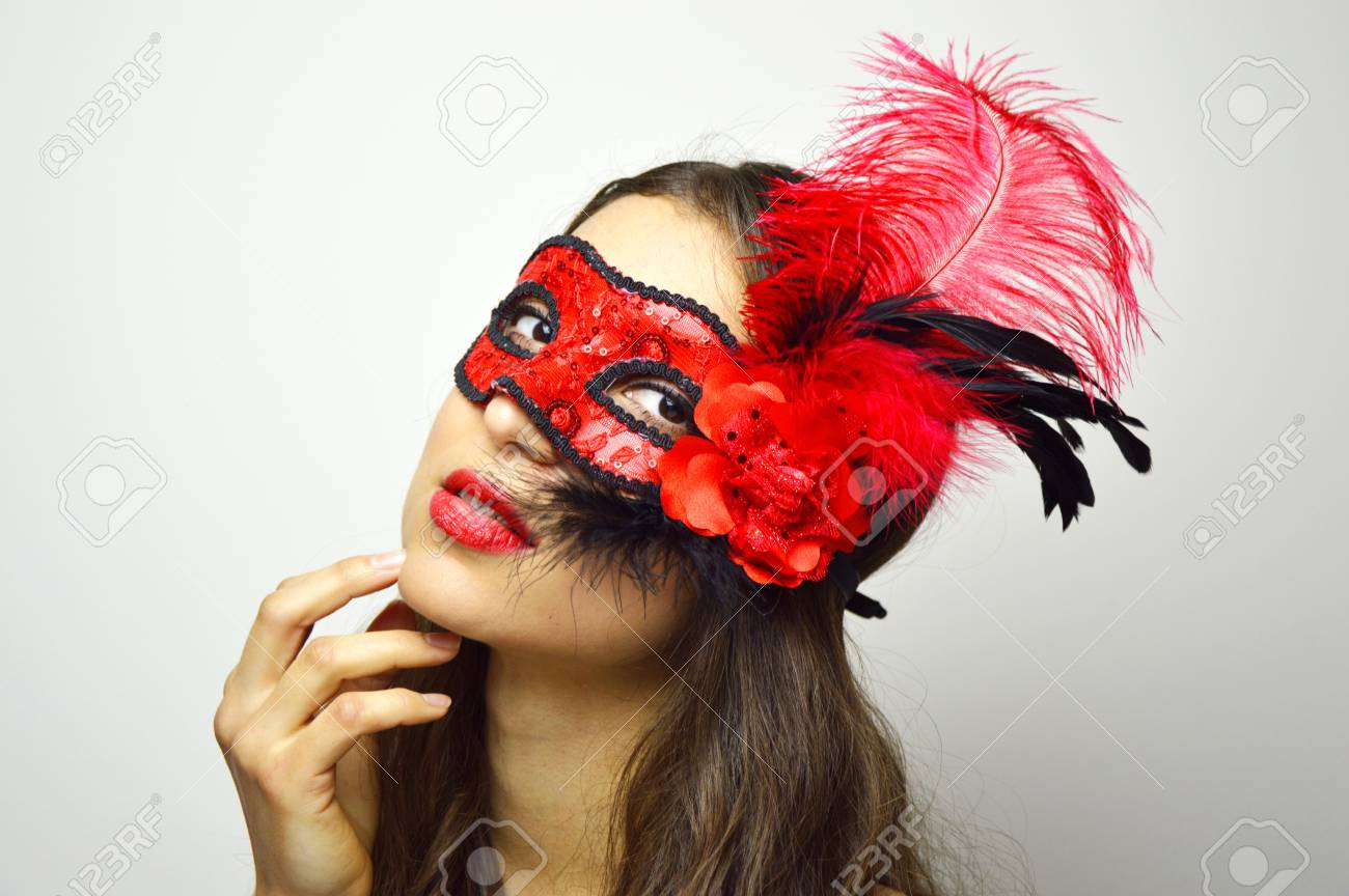 3025c26846979 Close up of sexy woman in mysterious Venetian mask looking at camera.  Attractive girl with red flowery carnival mask. Beauty female ready for  carnival night ...