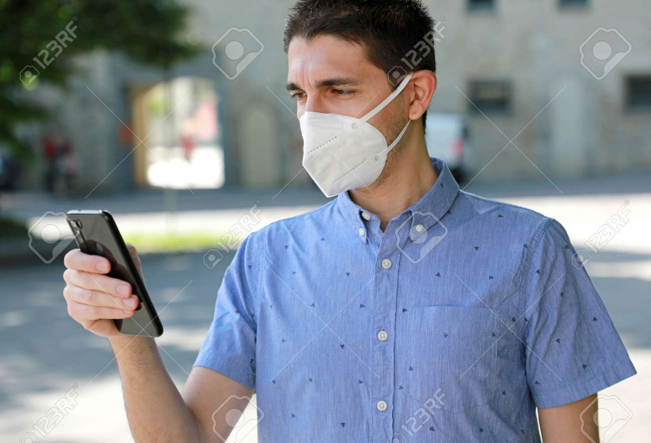 COVID-19 Mobile Application Young Man Wearing KN95 FFP2 Mask Using Smart Phone App in City Street to Aid Contact Tracing and Self Diagnostic in Response to the Coronavirus Pandemic 2019 - 147558565