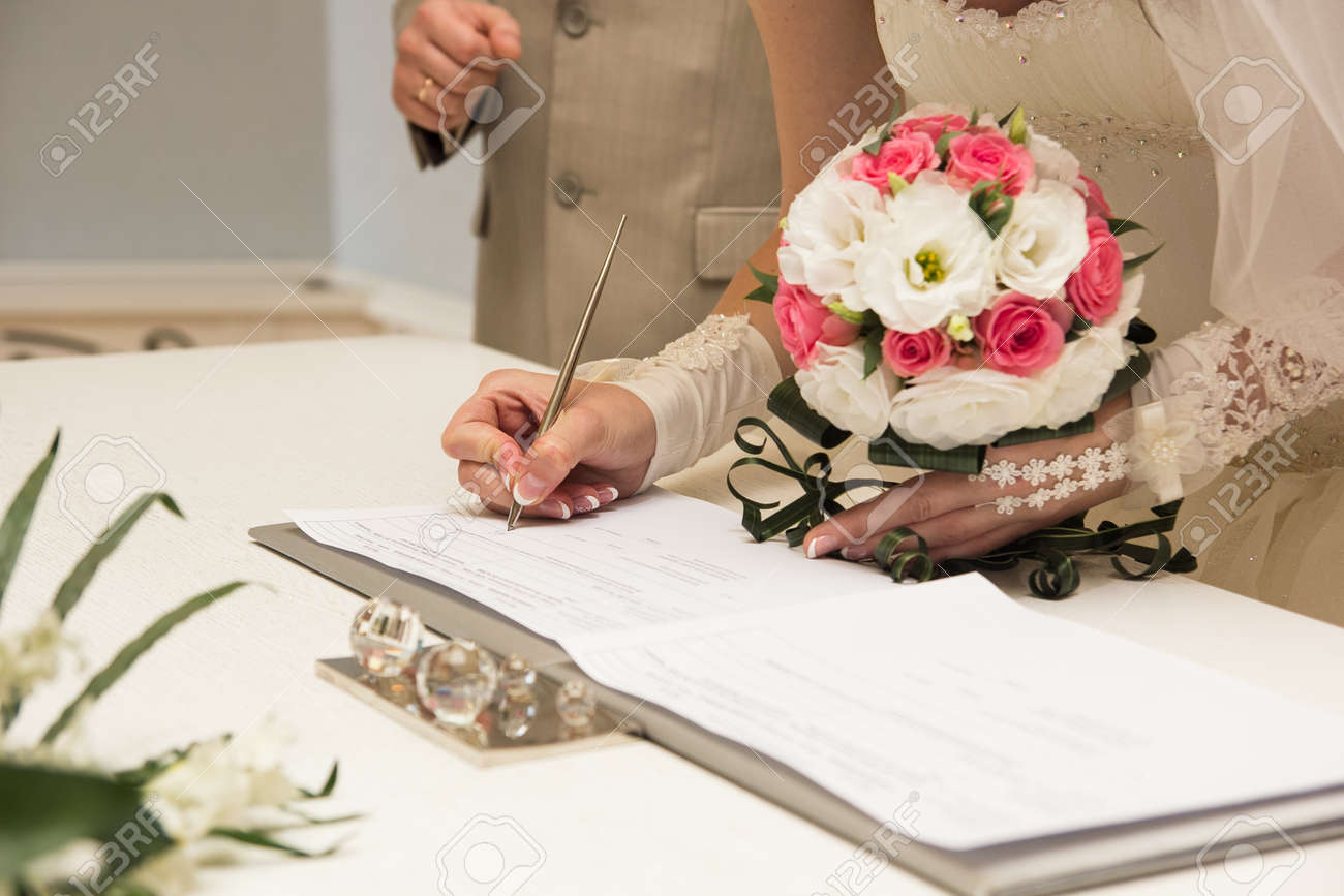 Brides hand closeup signing a wedding contract - 17774728