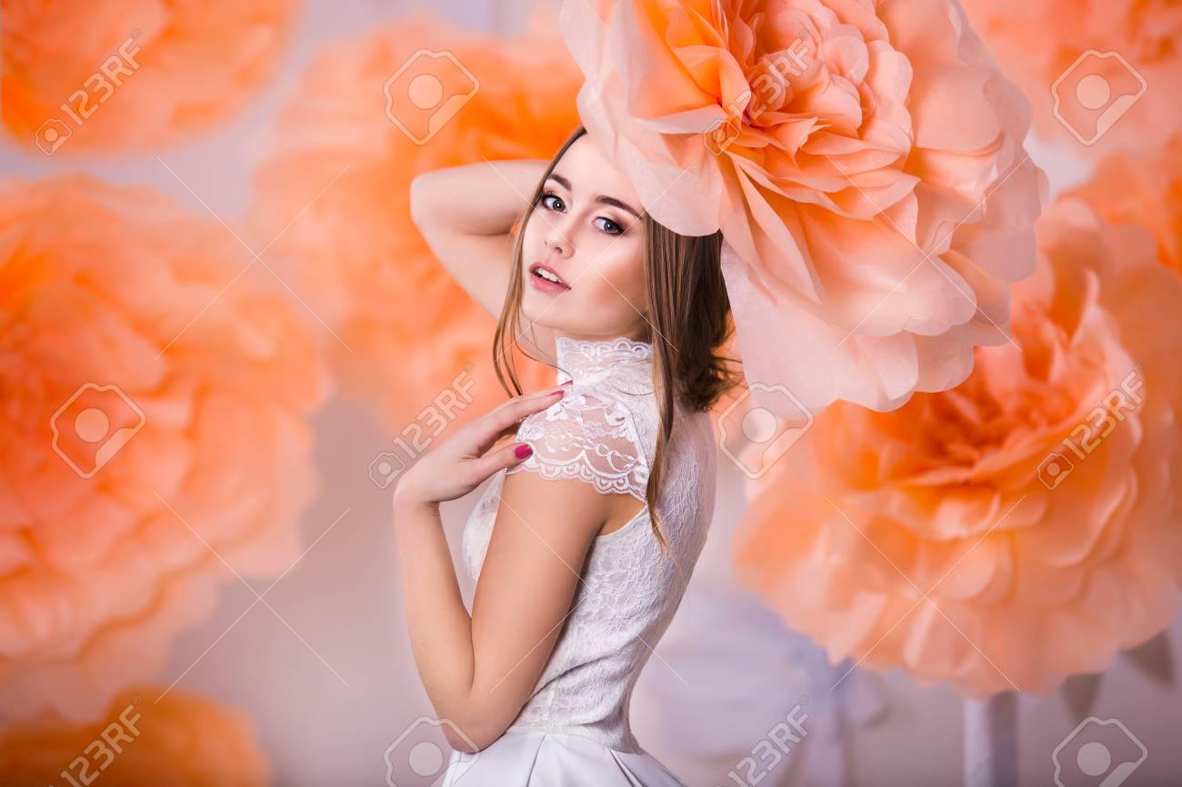 Young beautiful girl posing in paper flowers in spring studio - 38432457