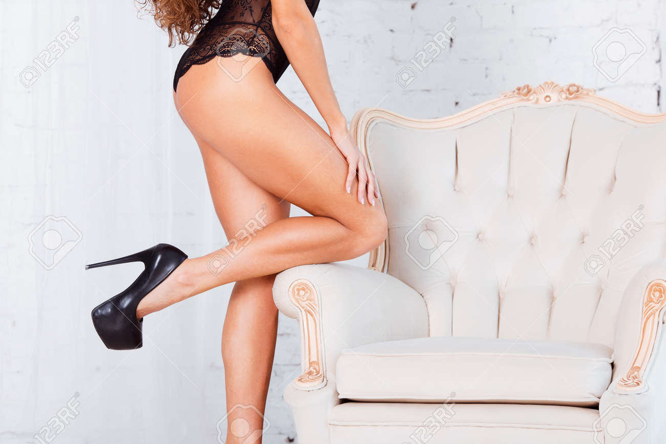 Perfect, sexy legs and ass of young woman wearing seductive black lingerie  Stock Photo -