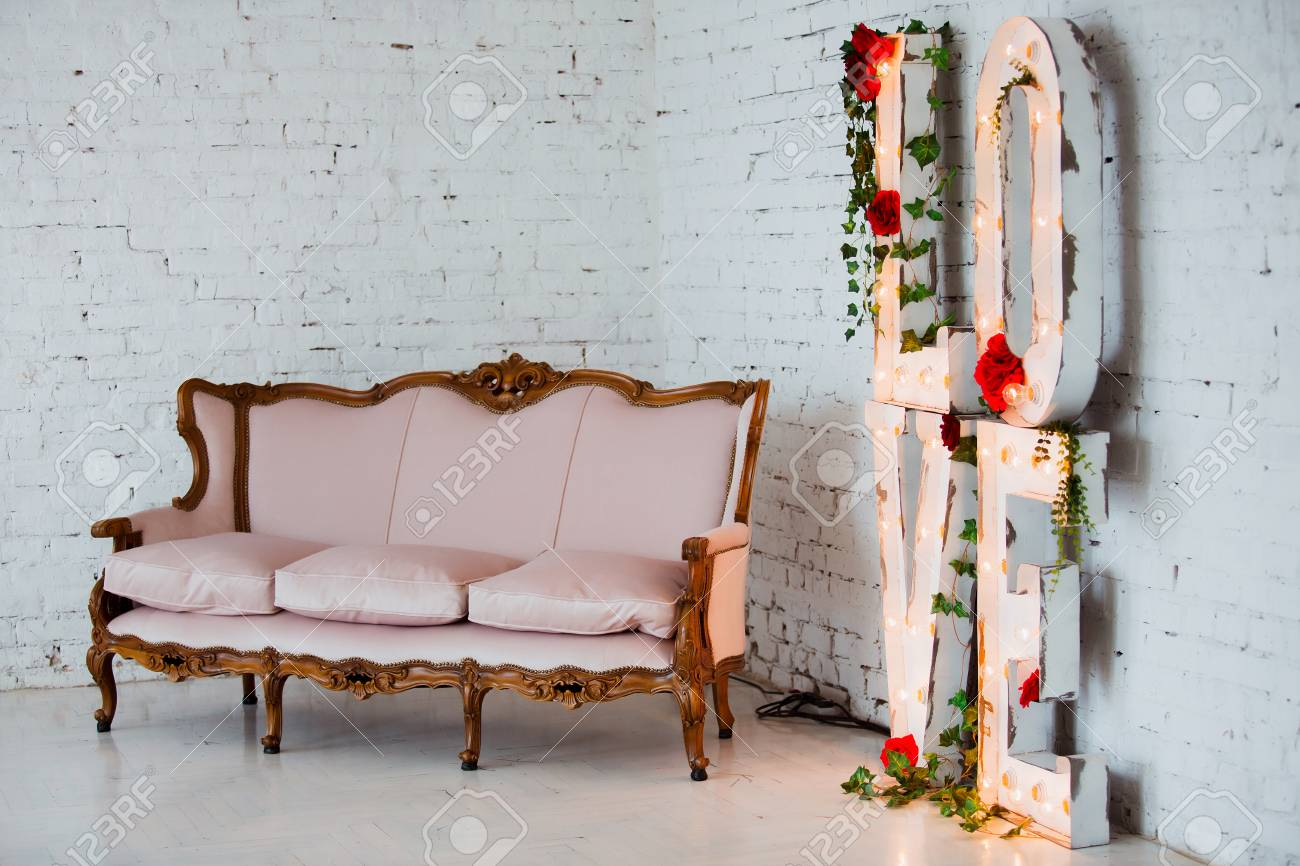 Stock Photo   Vintage Style Sofa Decorated With Flowers In Loft Interior  Room With Big Window.