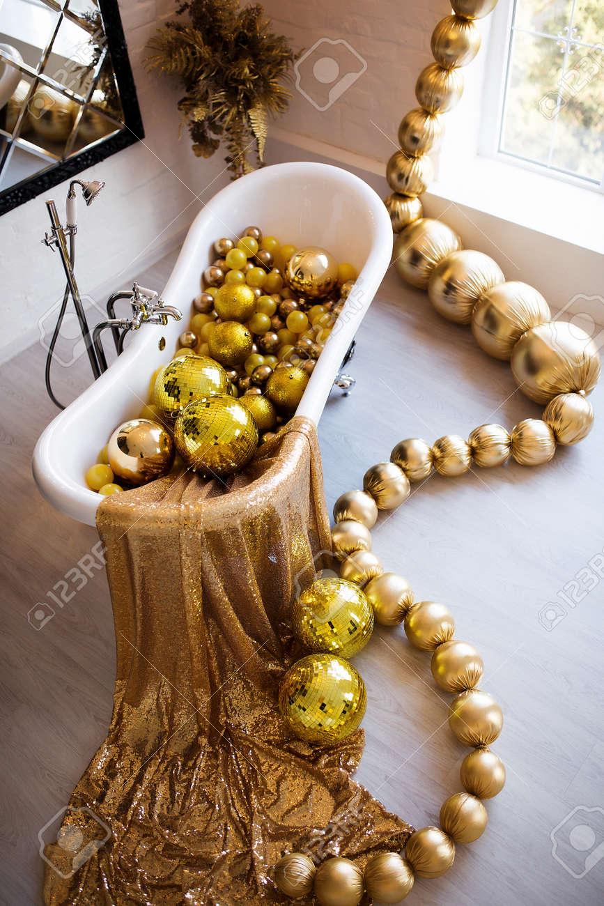 Vintage bright bathroom with black bath and mirror decorated with festive golden balls. Luxury bathroom interior. - 158318101