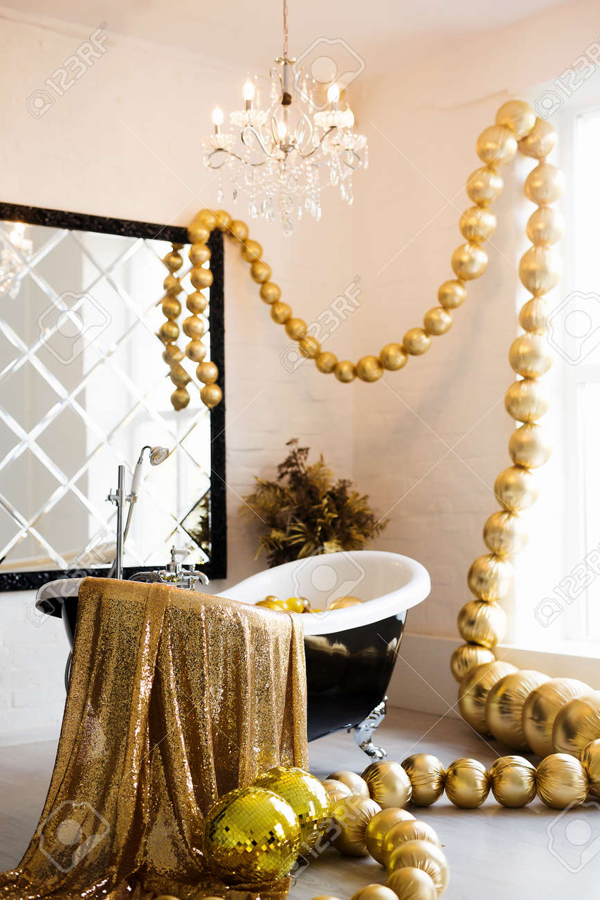 Vintage bright bathroom with black bath and mirror decorated with festive golden balls. Luxury bathroom interior. - 158318105