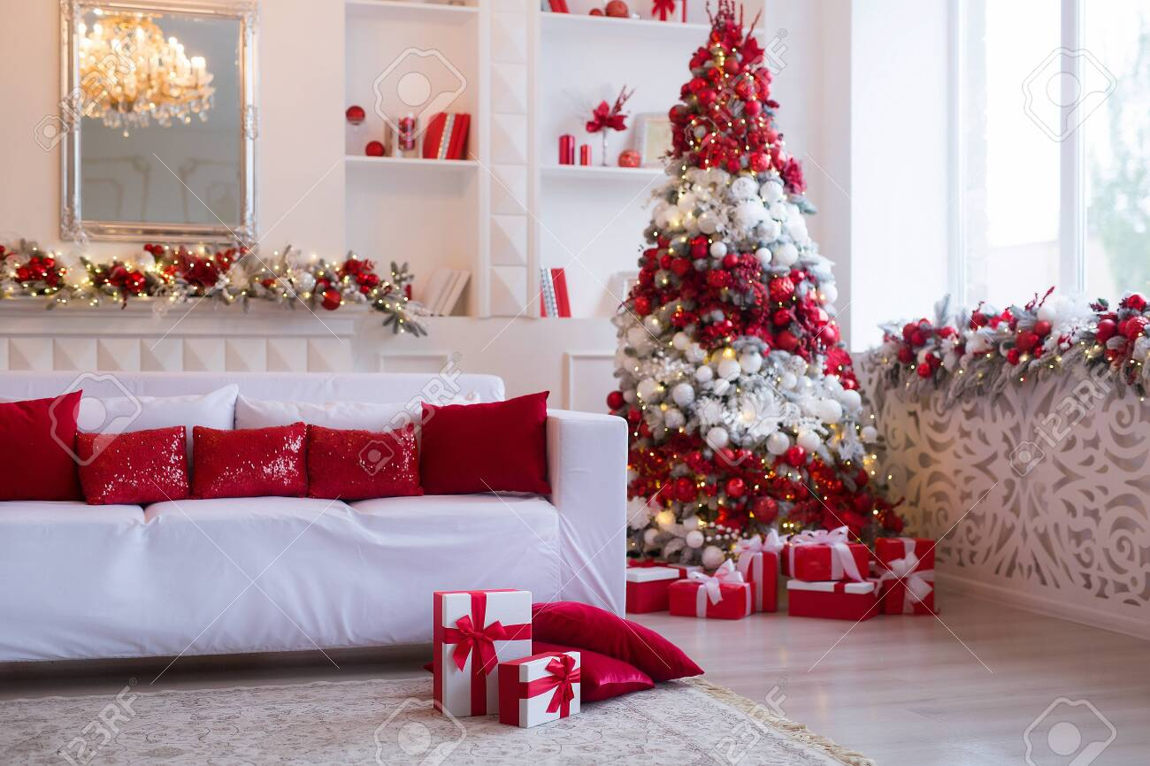 Interior of bright modern living room with fireplace and comfortable sofa decorated with Christmas tree and gifts - 158639675