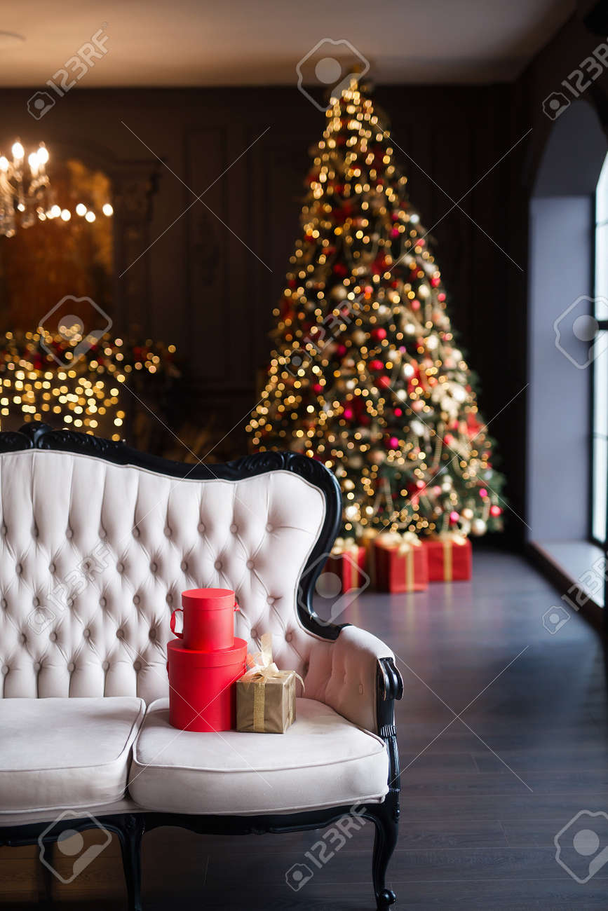 Interior of luxury dark living room with fireplace, comfortable sofa and chandelier decorated with Christmas tree and gifts - 158640790