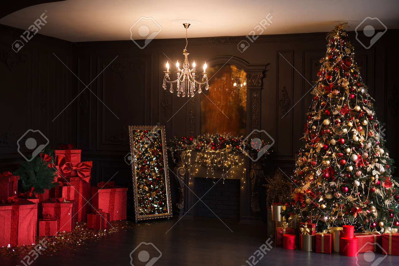 Interior of luxury dark living room with fireplace and chandelier decorated with Christmas tree and gifts - 160565958