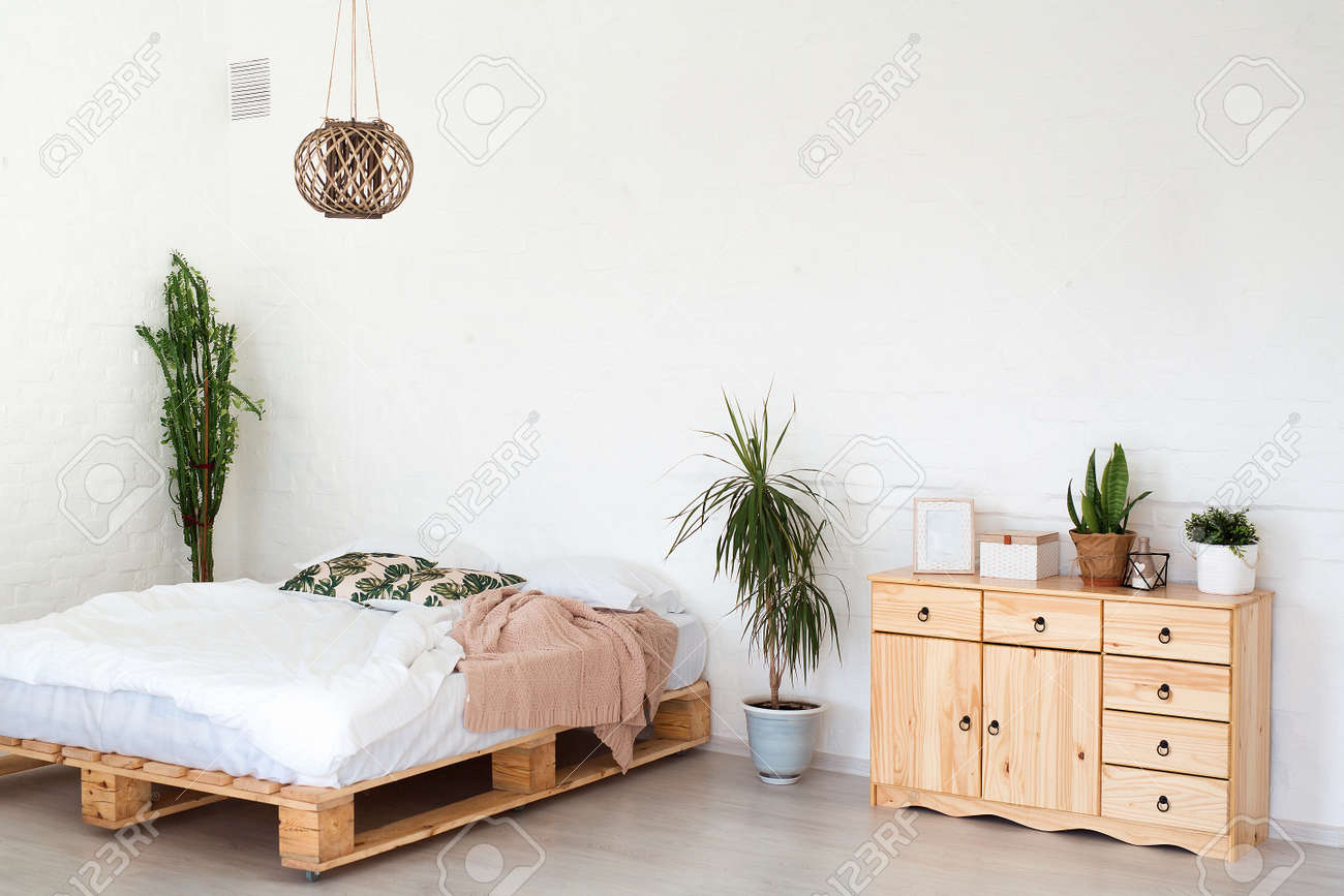 Cozy interior design of modern studio apartment in Scandinavian style. A spacious huge room in light colors with wooden bed and stylish expensive luxury furniture. - 163563521