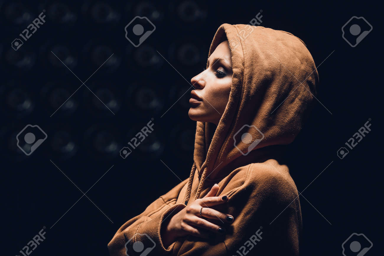 Studio portrait of a girl in a hoodie on a dark background - 165104330