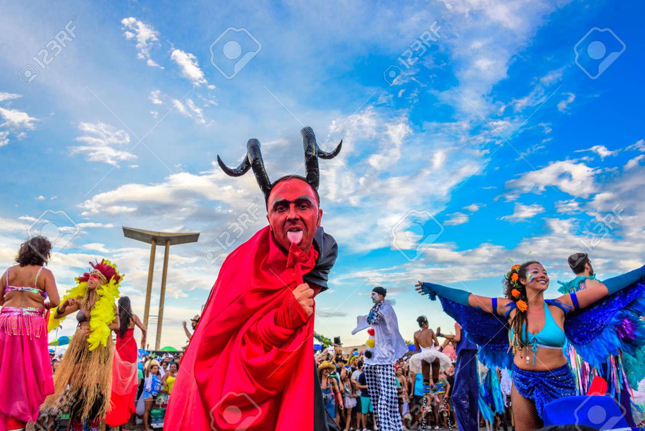 5694617c5962 RÍO DE JANEIRO, BRASIL - 28 de febrero de 2017: Hombre joven sobre pilotes  con un traje de diablo con cara roja, grandes cuernos negros y capa negra  ...