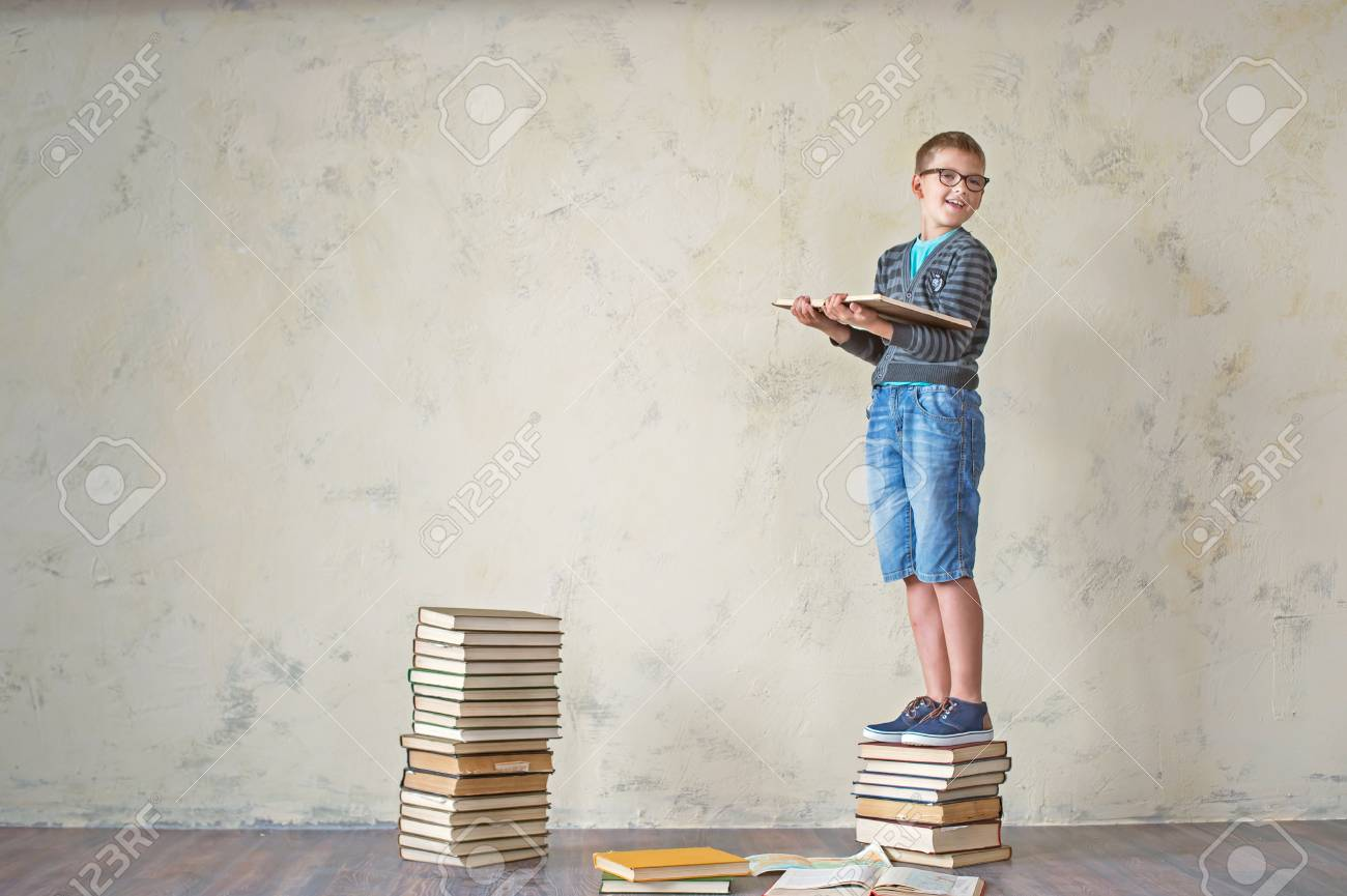 El Estudiante Del Muchacho En Pantalones Cortos Y Zapatillas De Deporte Un Sueter Que Se Sienta En Una Pila De Libros Y La Lectura Sobre Un Fondo De Color Amarillo Concepto De
