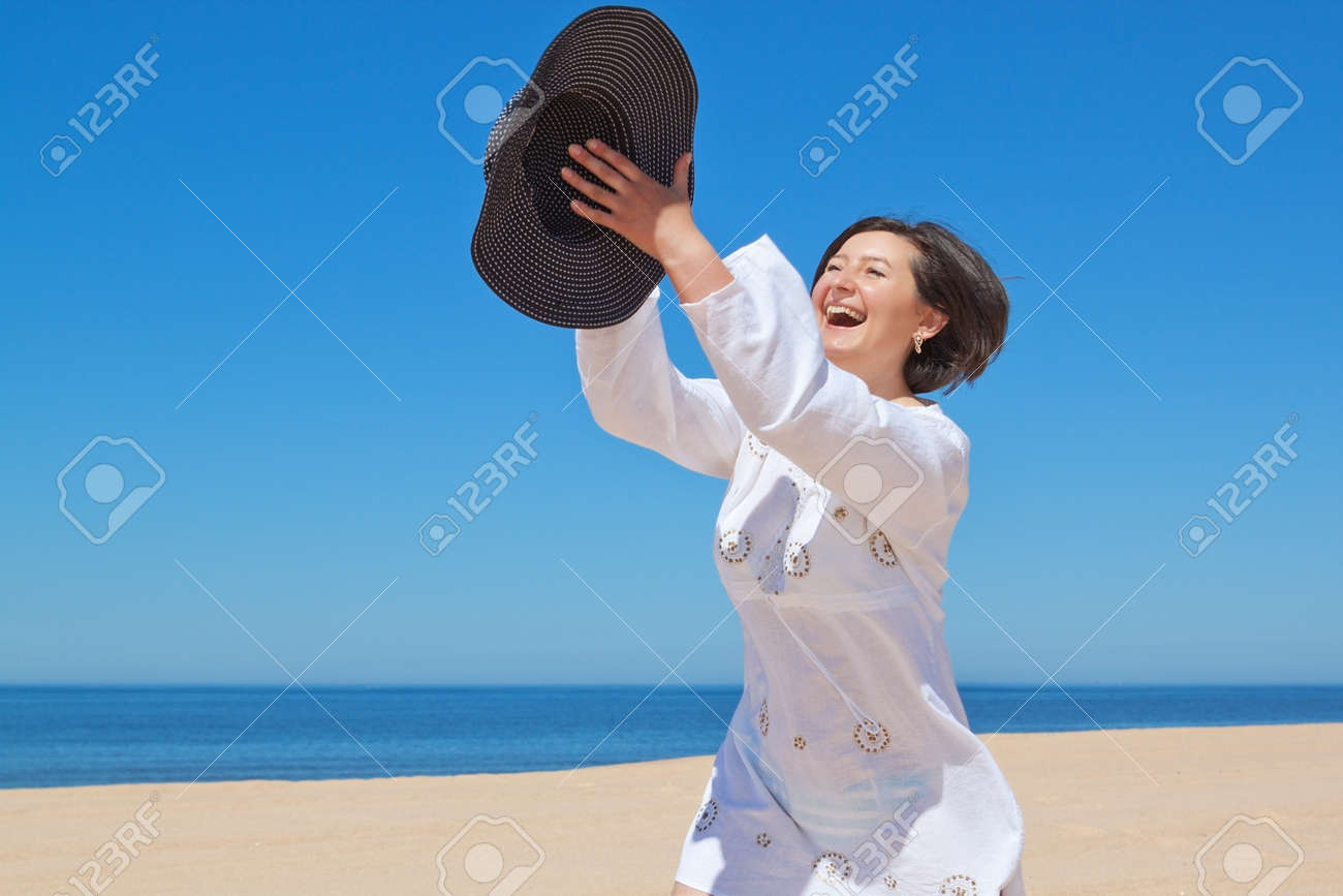 The girl on the beach playing with his hat Stock Photo - 14389724