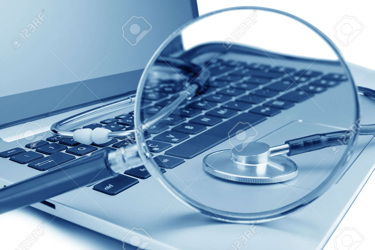 Tools for diagnostics on the laptop. Through a magnifying glass. Stock Photo - 19855296
