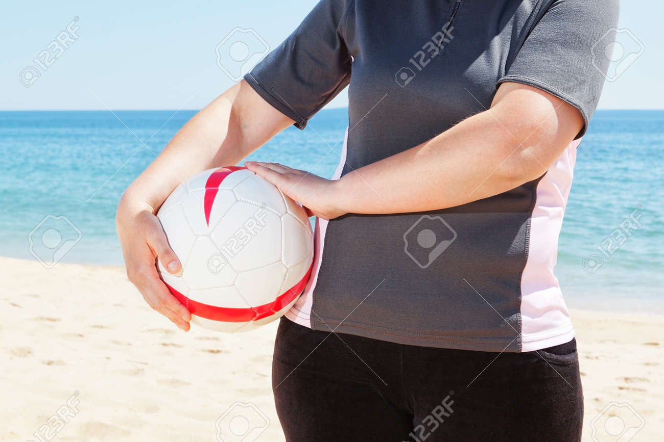 The girl on the beach holding a ball. Close-up. Stock Photo - 20591155