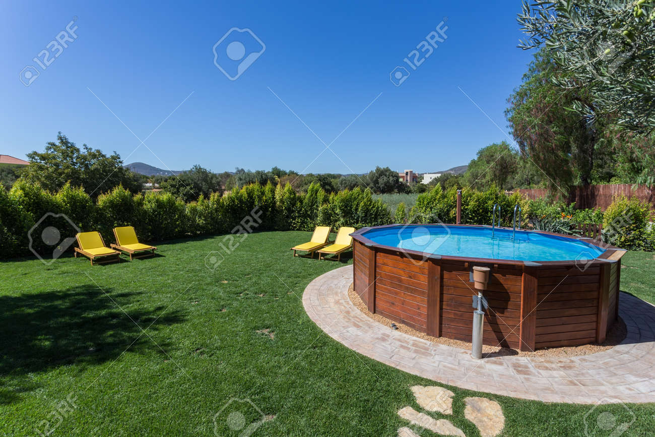 An above ground pool sets on a concrete pad in the backyard on a sunny summer day. - 58047889
