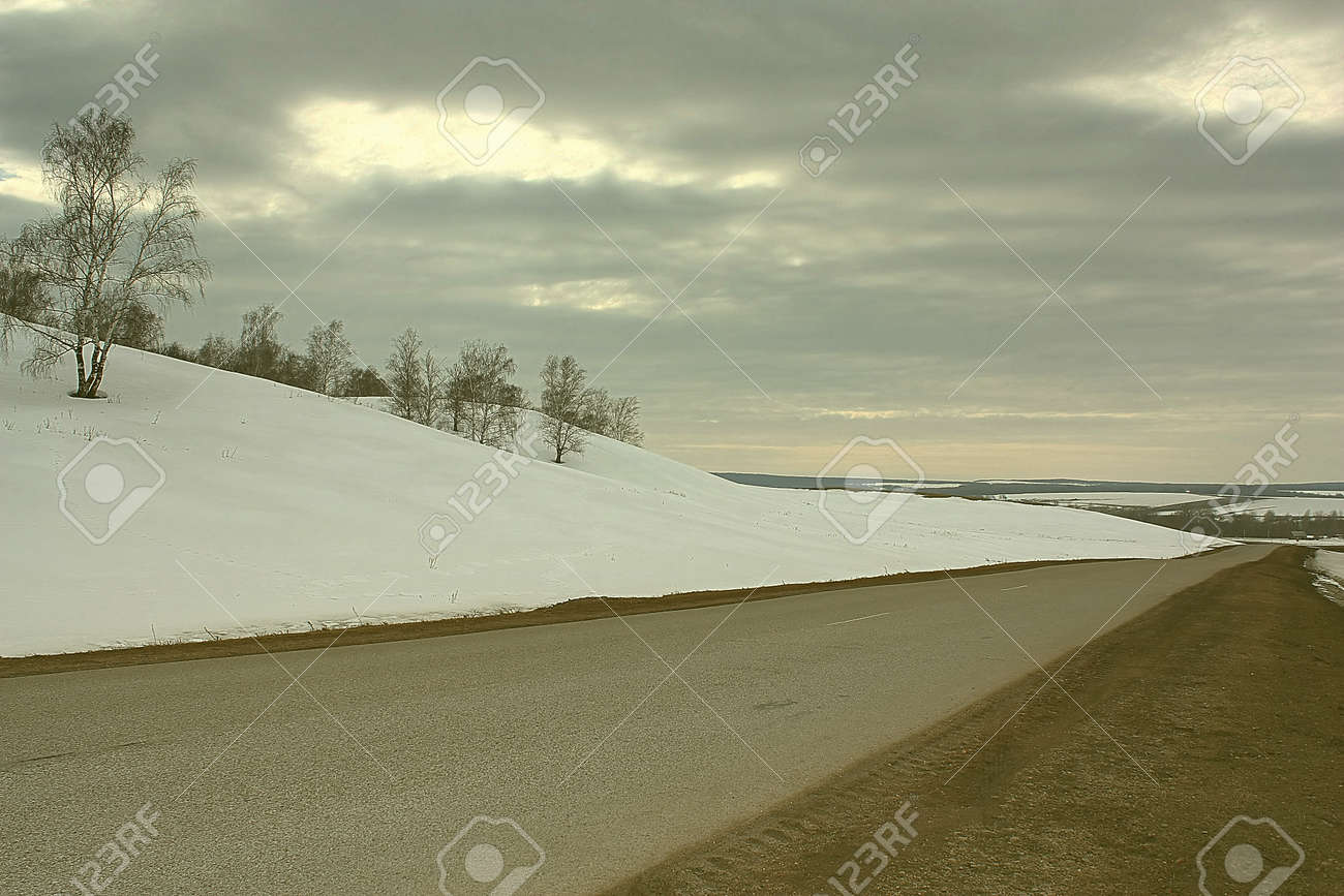 Spring countryside road and land with snow Stock Photo - 53216144
