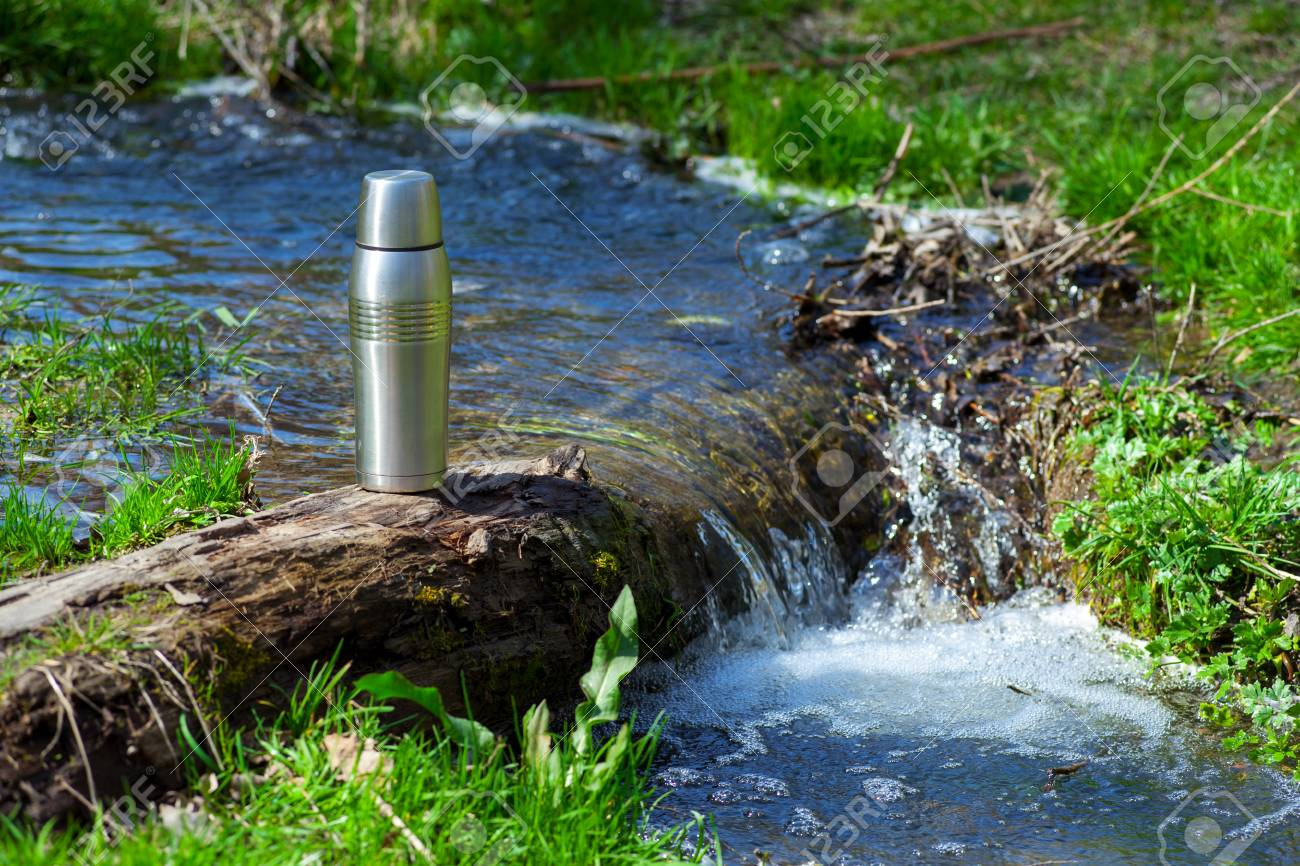 vacuum flask of coffee a tourist standing on a log by the river