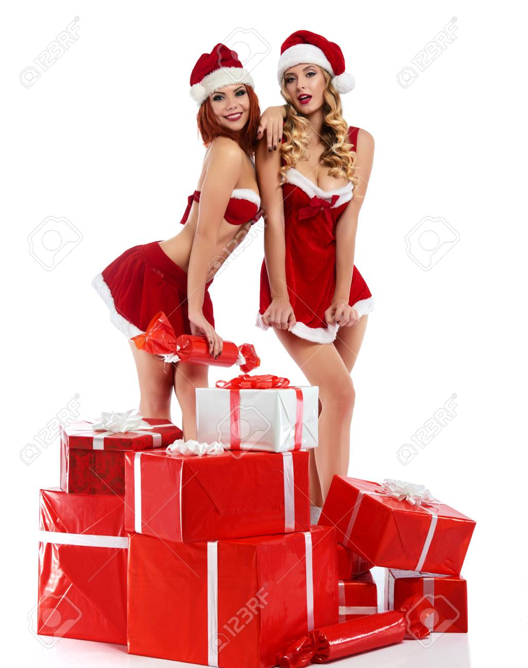Stock Photo - Two sexy Christmas girls posing with a pile of presents