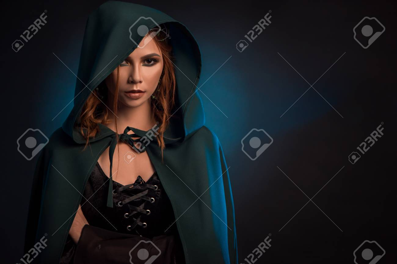 Mystic Girl Posing On Dark Studio Background Wearing Green Cape