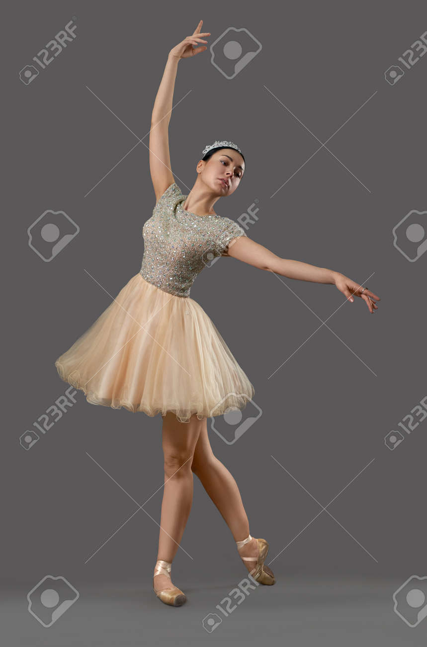 uk availability fdc28 ef696 Beautiful ballerina in beige dress, ballet shoes and crown dancing..