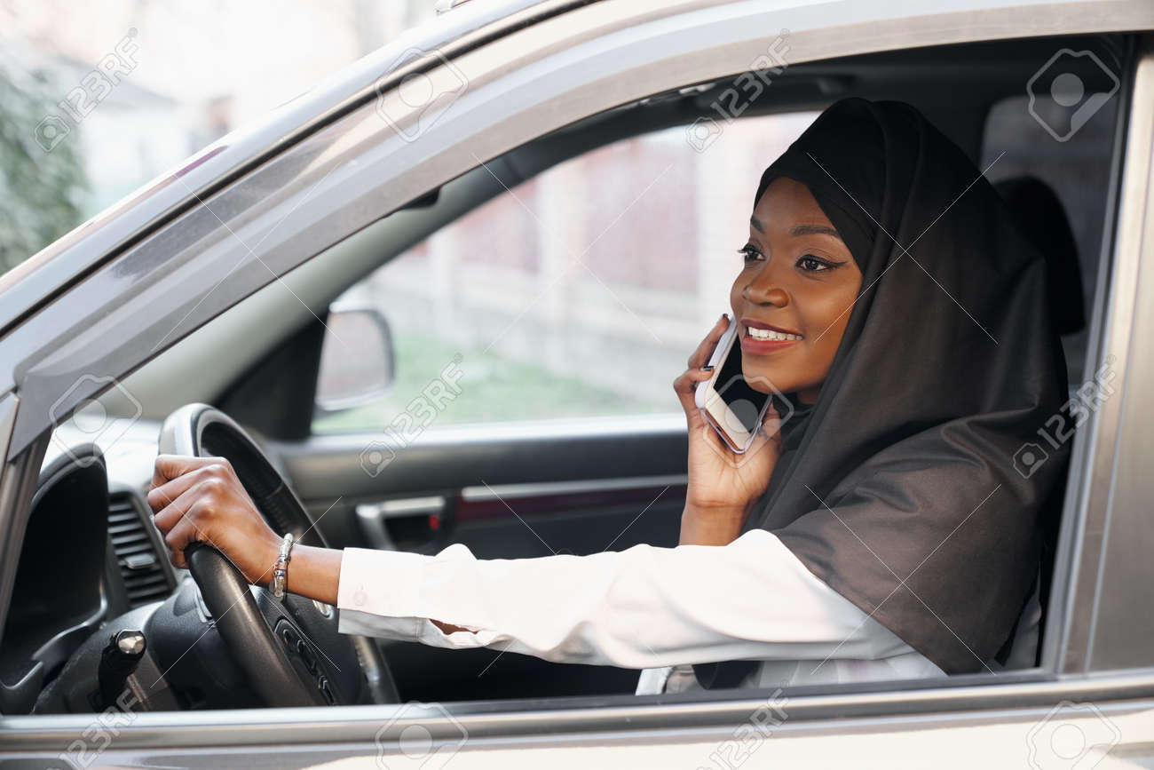 View from open window of young muslim woman talking by phone while driving car. Beautyful religious lady sitting in black salon, keeping wheel and laughing. Concept of vehicle and car. - 133752799