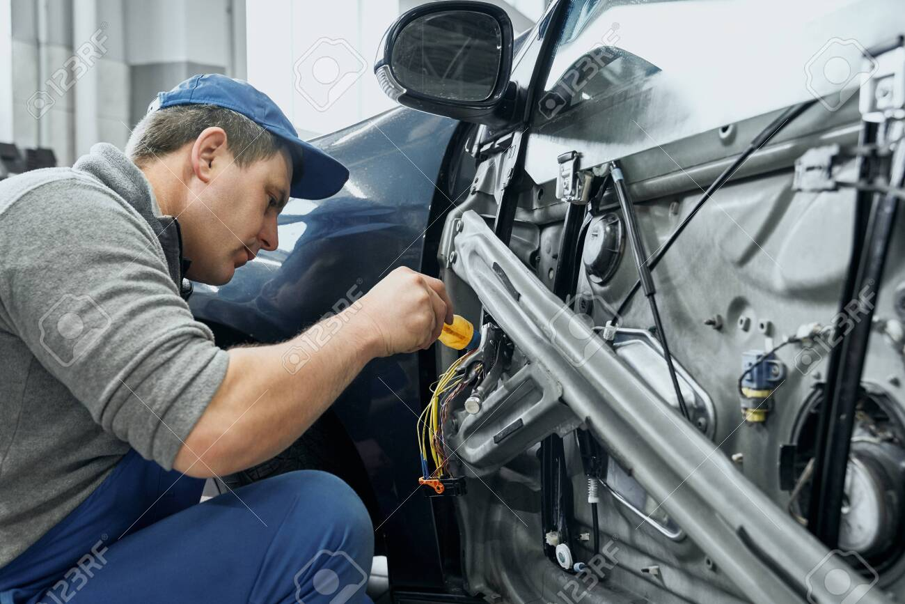 Side view of auto mechanic in blue uniform and cap repairing electrical wires in door of old car. Middle aged man changing damaged details to new ones in car service station - 133752810
