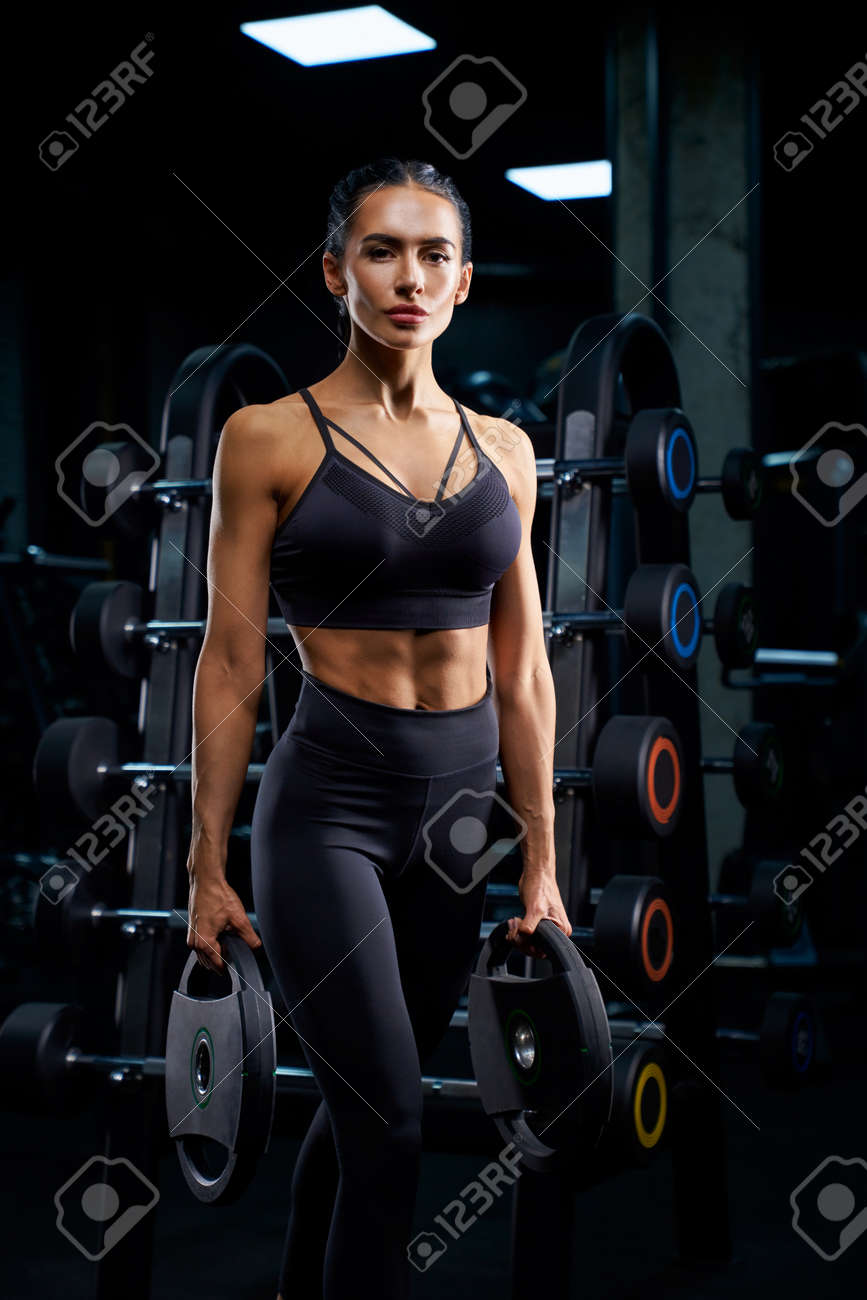Portrait of fitnesswoman with braids posing near stand with sports equipment and holding weights. Srtong woman with muscular body standing in gym in dark atmosphere, looking at camera. - 139355121