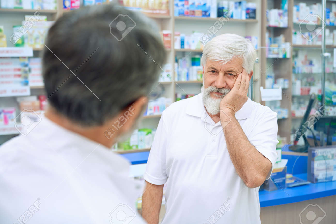Selective focus of senior man with tooth ache consulting with pharmacist. Back view of unrecognizable man in white uniform offering medicineswhile eldery male customer frowning painfully. - 148723363