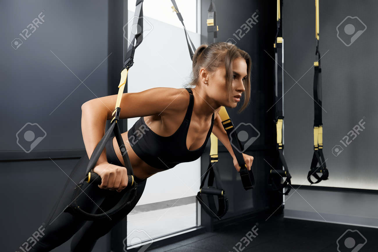 Side view of young woman doing workout exercise with trx system. Concept of training with fitness straps in modern gym. - 164897662