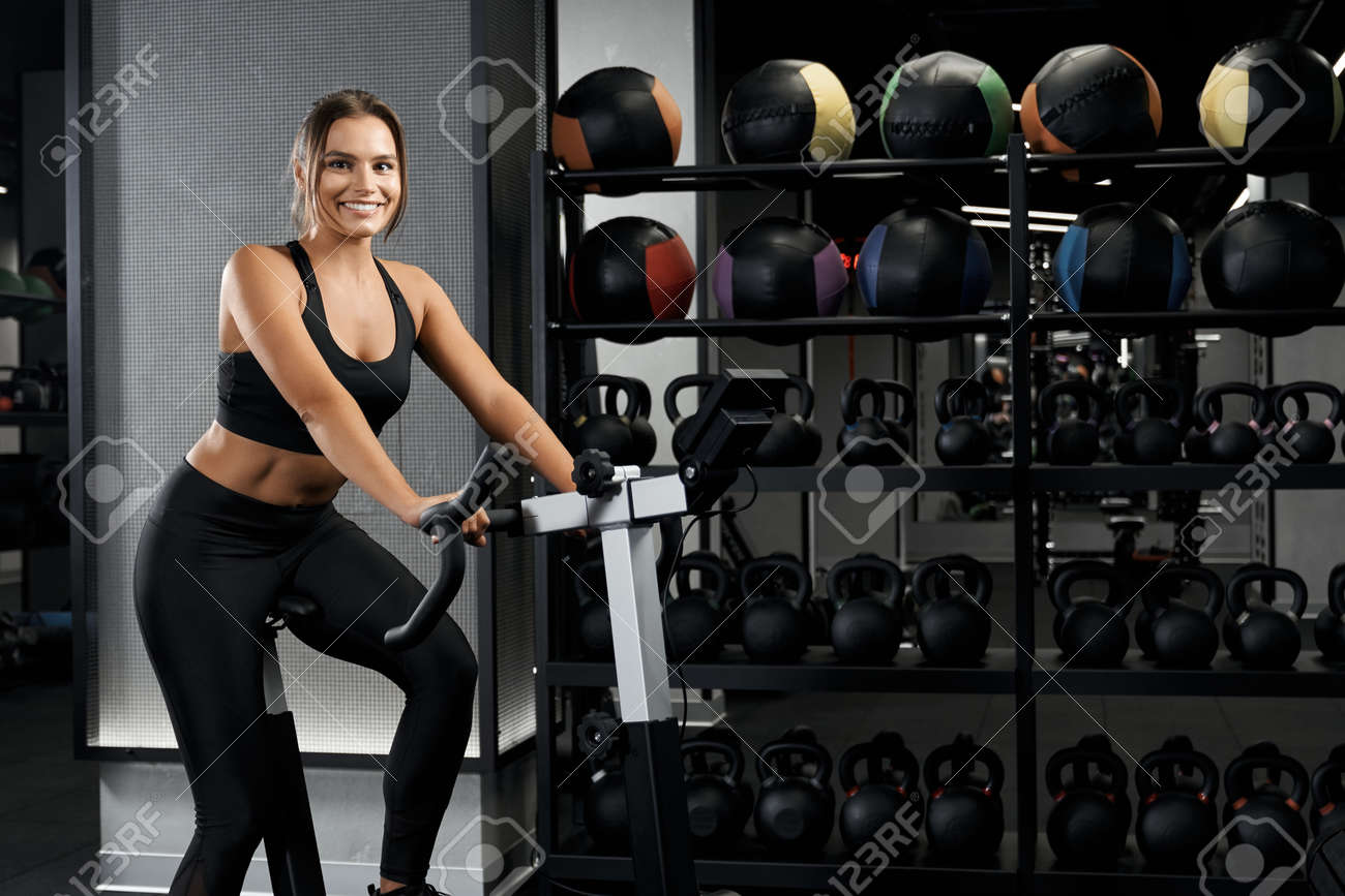 Smiling beautiful young woman in black sportswear engaged on exercise bike. Concept of active lifestyle and pump up body. - 165477573