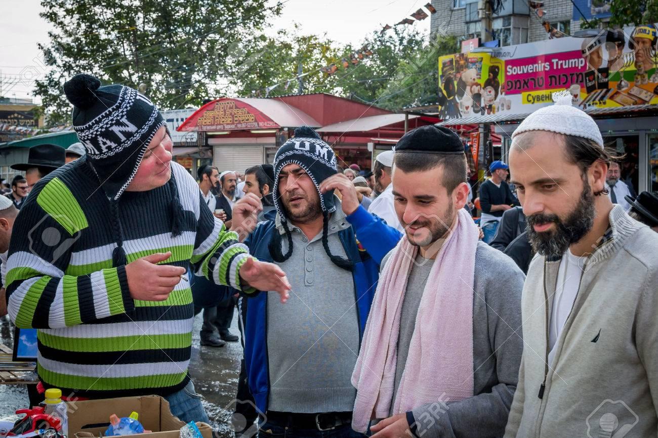 Uman, Ukraine - 2 octobre 2016: Rosh Hashanah, nouvelle année juive 5777. Les pèlerins de Hasidim en tenue festive traditionnelle célèbrent la messe sur l'Uman. Vendeurs de souvenirs. Banque d'images - 84306495
