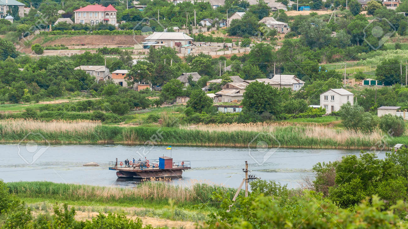 Ukraine, Southern Bug River - 18 june 2017: Ferry crossing. The ferry moves with the help of a man's muscular strength. Repels from the steel cable. Such a ferry is unique in Ukraine. Banque d'images - 84598261